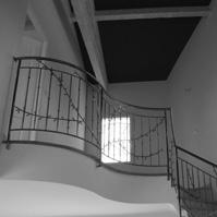 Photo intérieure : escalier, garde corps en ferronerie, charpente bois apparente.<br />