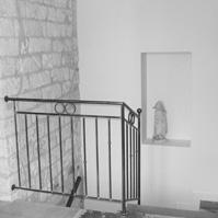 Cage d&rsquo;escalier avec garde corps en ferronnerie.</p>