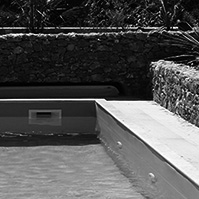 Petite piscine clôturée par de petits murets en bois<br />
