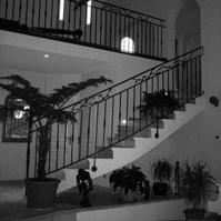 Escalier intérieur carrelé avec garde corps en fer forgé.<br />