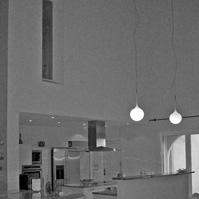 Espace cuisine avec ilot central et bar. Grande hauteur sous plafond. charpente bois apparente en lamellé collé.<br />