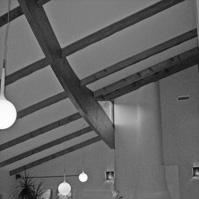 Espace salon avec cheminée maçonnée. Grande hauteur sous plafond. charpente bois apparente en lamellé collé.<br />