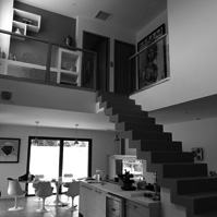 Escalier en béton ciré aux lignes épurées au dessus de la cuisine.<br />
