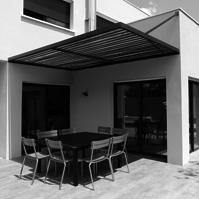 Espace repas sur la terrasse extérieure protégée du soleil par une pergola métal et bois.<br />