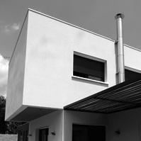Espace repas sur la terrasse extérieure protégée du soleil par une pergola métal et bois. Conduit de fumée extérieur en inox.<br />
