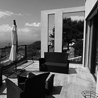 Terrasse façade Sud avec sièges en osier, barrières en verre et vue sur la mer<br />