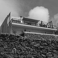 Vue globale de la façade Sud de la villa avec mur en pierre délimitant le terrain<br />