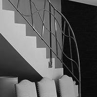 Escaliers avec rampe en métal et mur en pierre</p>